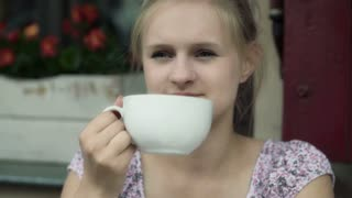 Beautiful girl drinking coffee and smiling to the camera in the cafe