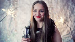 Beautiful girl holding glass with schampagne and smiling to the camera
