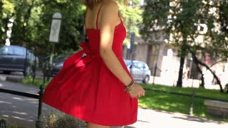 Beautiful girl in red dress moving around and enjoying this, slow motion shot at