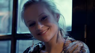 Beautiful girl sitting next to the window and smiling to the camera, steadycam s