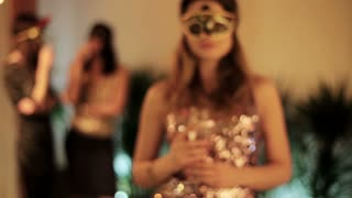 beautiful woman in a mask toasting and drinking wine to the camera