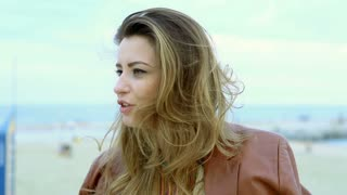 Beautiful woman sitting at the sea and chatting, steadycam shot, slow motion sho
