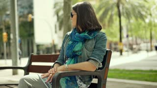 Beautiful woman sitting on the bench and showing thumbs to the camera, steadycam