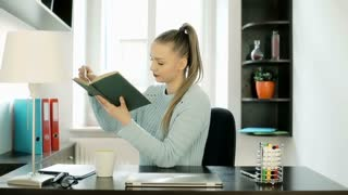 Beautiful woman sitting on the swivel chair in her office and reading book, stea
