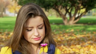 Beautiful woman smelling flower in the autumnal park