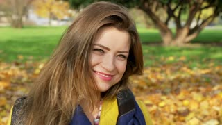 Beautiful woman smiling to the camera in the autumnal park