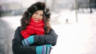 Beautiful woman standing in the snowy park and smiling to the camera