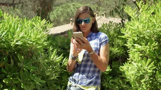 Beautiful woman using smartphone next to the bushes and smiling to the camera