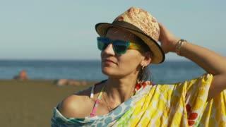 Beautiful woman walking on the sandy beach next to the sea, steadycam shot