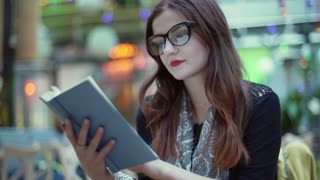 Beautiful woman wearing glasses and reading book, steadycam shot