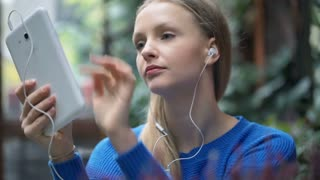 Blonde girl listening music and browsing internet on tablet