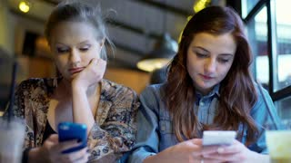 Bored friends sitting in the cafe and browsing internet on smartphone