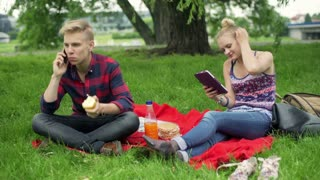 Boy chatting on cellphone and girl using tablet on the picnic