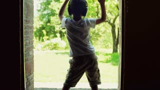 Boy dancing in the doors with the view on garden and listening music, steadycam