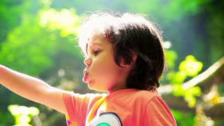 Boy eating and walking in forest, steadycam shot, slow motion shot at 240fps