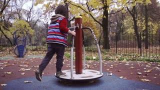 Boy having fun on playground in the park, steadycam shot, slow motion shot
