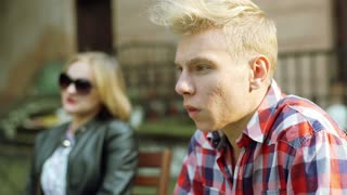 Boy looking morose and talking with his girlfriend