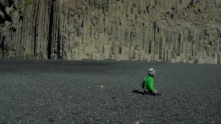 Boy play on Reynisfjara beach at south coast of Iceland, slow motion shot