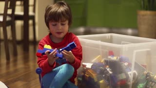 Boy playing with toys in the room, steadycam shot, slow motion shot at 100fps