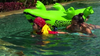 Boy pulling his mother on toy in the swimming pool, slow motion shot at 240fps