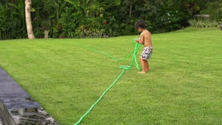 Boy pulling hose and playing with it in the garden, slow motion shot at 240fps