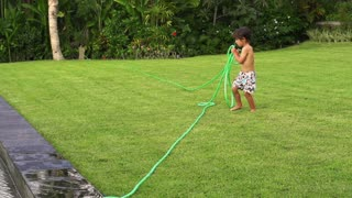 Boy pulling hose and playing with it in the garden, slow motion shot