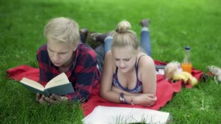 Boy reading book and helping his girlfriend with homework in the park