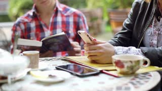 Boy reading book and his girlfriend using smartphone in the outdoor cafe