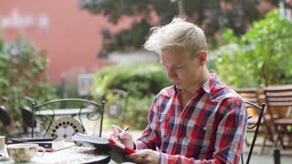 Boy sitting in the outdoor cafe and writing something in notebook