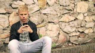 Boy sitting next to the brick wall and texting on smartphone