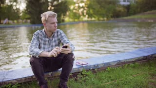 Boy sitting next to the pond and doing selfies on smartphone