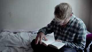 Boy sitting on the bed and reading absorbing book
