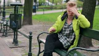 Boy sitting on the bench in the park and having a headache