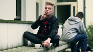 Boy smoking cigarette and using cellphone in the public place