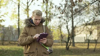 Boy standing in the autumnal park and browsing internet on tablet