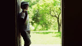 Boy standing in the doors with the view on garden and eating snack, steadycam sh