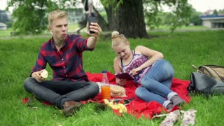 Boy taking selfie and girl using tablet on the picnic