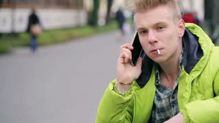Boy talking on cellphone and smoking cigarette in the park