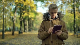 Boy using tablet in the autumnal park and smiling to the camera