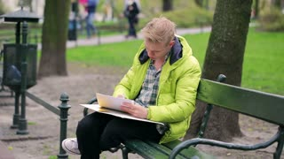 Boy writing something on the papers in the park
