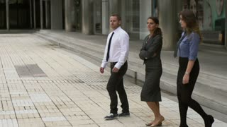 Business people walking on public square, slow motion shot at 240fps, steadycam