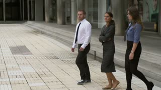 Business people walking on public square, slow motion shot, steadycam shot