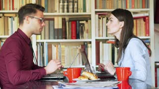 Businesscouple talking and working together at home