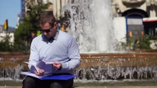 businessman checking documents and sitting by fountain, slow motion