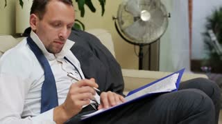 businessman checking documents and sitting on the sofa at home