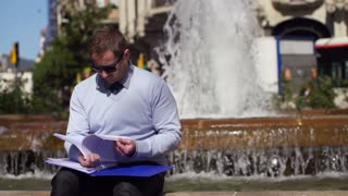 businessman checking documents by fountain, slow motion shot at 240fps