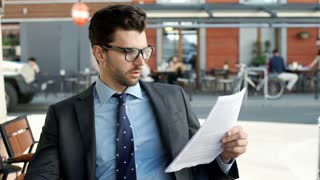 Businessman checking papers and doing serious look to the camera, steadycam shot