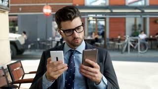 Businessman comparing information on two smartphones, steadycam shot