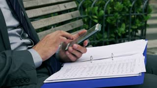 Businessman counting data on cellphone, closeup, steadycam shot