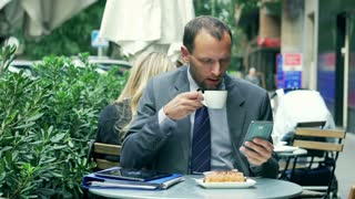 Businessman drinking coffee in the street cafe and using cellphone